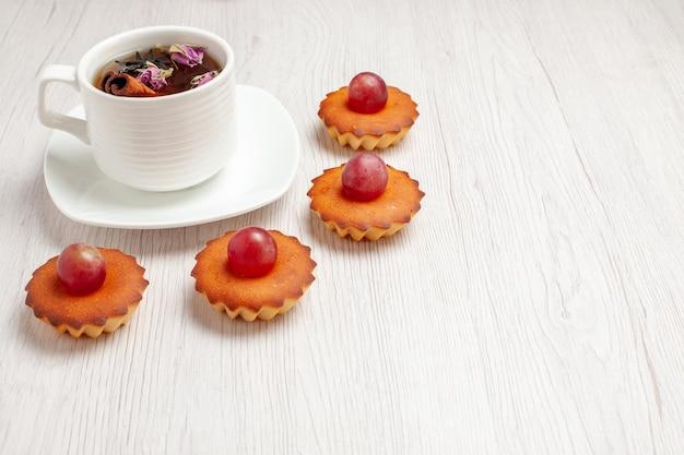 Vista frontal de bolinhos deliciosos com xícara de chá no fundo branco frutas chá sobremesa biscoito biscoito torta de bolo