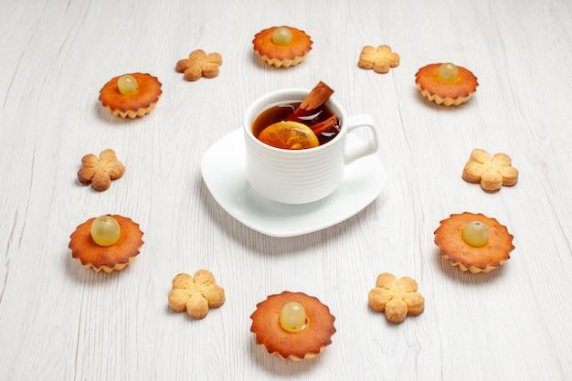 Vista frontal de bolinhos deliciosos forrados com biscoitos e xícara de chá no chão branco