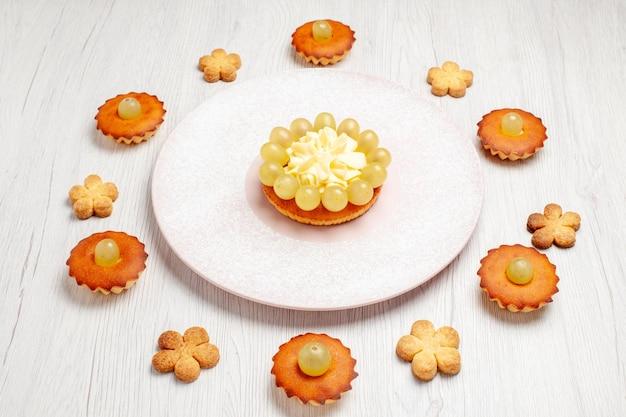 Vista frontal de bolinhos deliciosos forrados em fundo branco sobremesa biscoito chá bolo torta doce