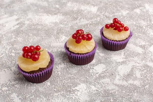 Vista frontal de bolos de chocolate com cranberries e anéis de abacaxi