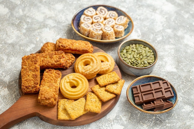 Vista frontal de bolos deliciosos com biscoitos no biscoito doce de mesa branca