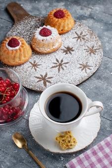 Vista frontal de bolos deliciosos com uma xícara de café e cranberries vermelhas frescas na mesa cinza