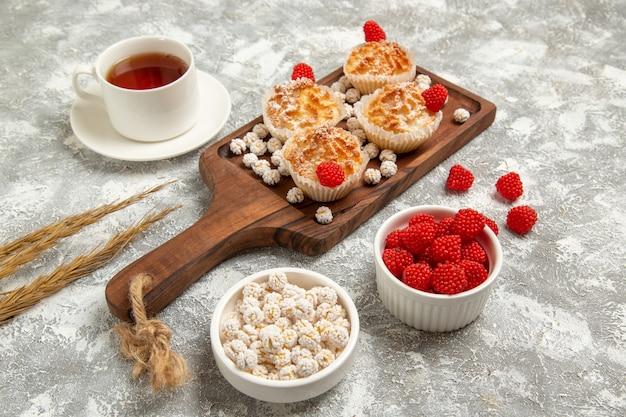 Vista frontal de bolos doces com balas e xícara de chá em uma superfície branca