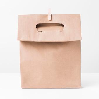 Vista frontal de bolsa de papel pardo e clipe de madeira