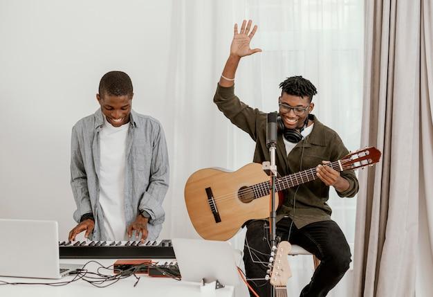 Vista frontal de bonitos músicos masculinos em casa tocando teclado elétrico e guitarra