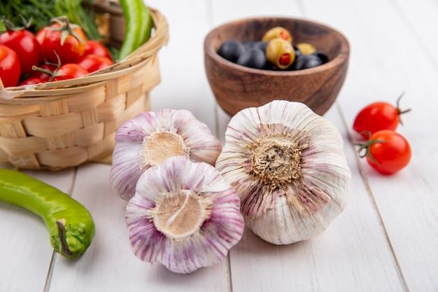Vista frontal de bulbos de alho com azeitonas na tigela e pimenta endro de tomate na cesta na superfície de madeira