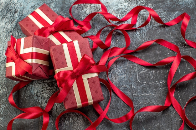 Vista frontal de caixas de presente lindamente embaladas e amarradas com fita na escuridão gelada