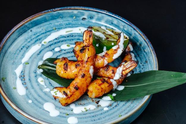 Vista frontal de camarão frito com molho num prato
