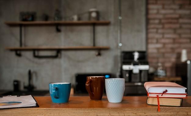 Vista frontal de canecas de café no balcão da mesa