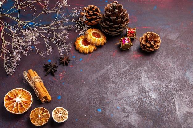 Vista frontal de canela e biscoitos no espaço escuro