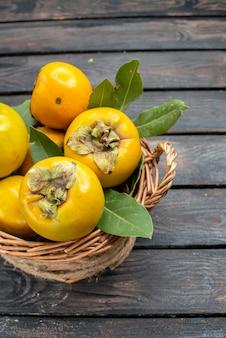 Vista frontal de caquis frescos frutas maduras doces na mesa de madeira