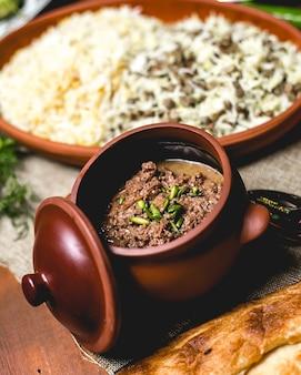 Vista frontal de carne assada com cebola em uma panela com arroz cozido