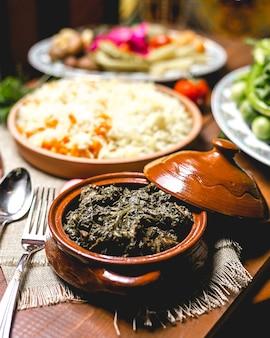 Vista frontal de carne assada com verduras em uma panela com arroz cozido