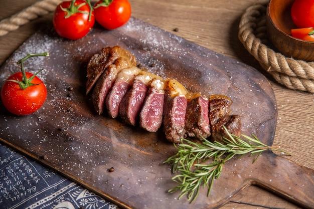 Vista frontal de carne fatiada frita com verduras e tomates vermelhos frescos na mesa de madeira