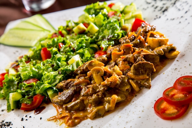 Vista frontal de carne frita com cogumelos em molho com salada de legumes e fatias de tomate e pepino