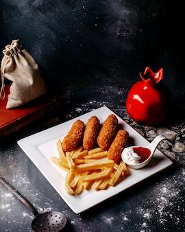 Vista frontal de carne frita junto com batatas fritas na superfície cinza