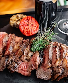 Vista frontal de carne grelhada com alecrim e uma fatia de tomate no quadro