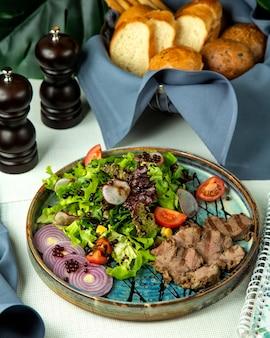 Vista frontal de carne grelhada com salada de legumes e cebola em uma bandeja Foto gratuita
