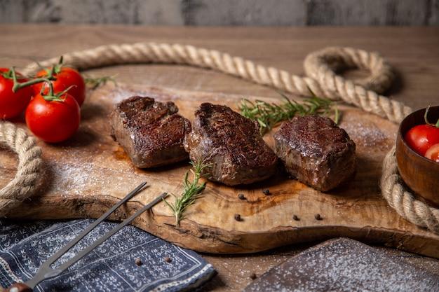 Vista frontal de carne saborosa frita com tomates vermelhos frescos e verduras na mesa de madeira