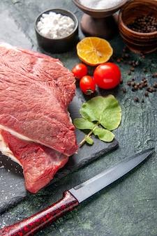 Vista frontal de carne vermelha crua fresca na bandeja pimenta preta sal limão faca martelo de madeira em fundo de cor escura