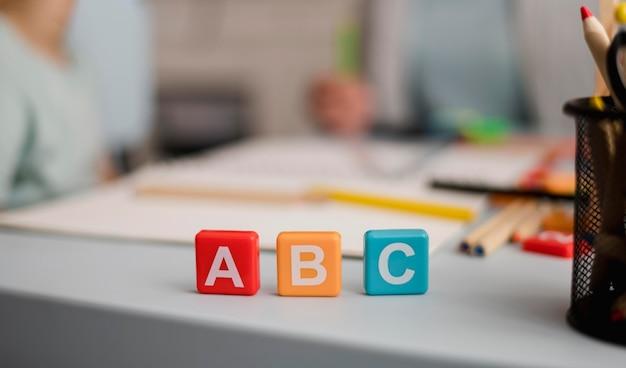 Vista frontal de cartas em cubos com sessão de tutoria desfocada nas costas