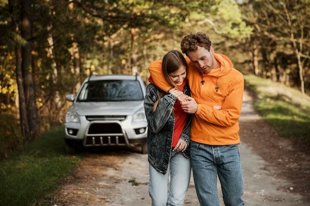 Vista frontal de casal abraçado ao ar livre em uma viagem