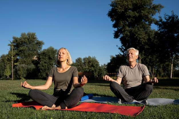 Vista frontal de casal de idosos praticando ioga ao ar livre