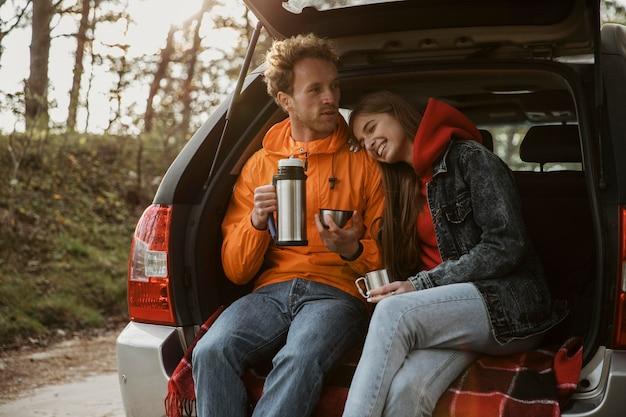 Vista frontal de casal desfrutando de uma bebida quente no porta-malas do carro