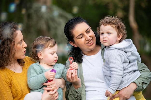 Vista frontal de casal lgbt ao ar livre com filhos