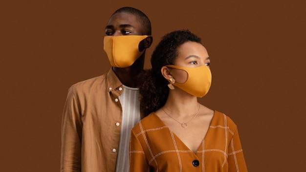 Vista frontal de casal posando com máscaras