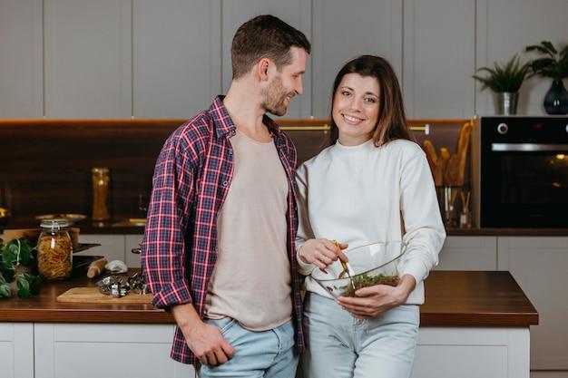 Vista frontal de casal preparando comida em casa