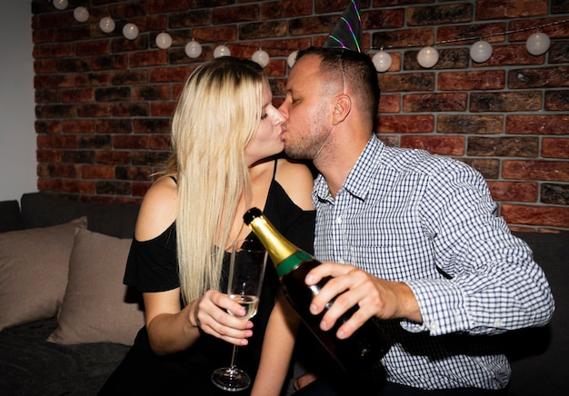 Vista frontal de casal se beijando na véspera de ano novo