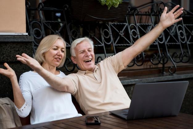 Vista frontal de casal sênior fazendo uma videochamada no laptop ao ar livre