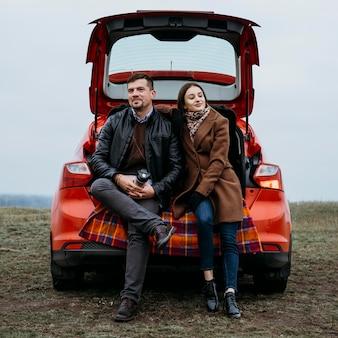 Vista frontal de casal sentado ao ar livre no porta-malas do carro