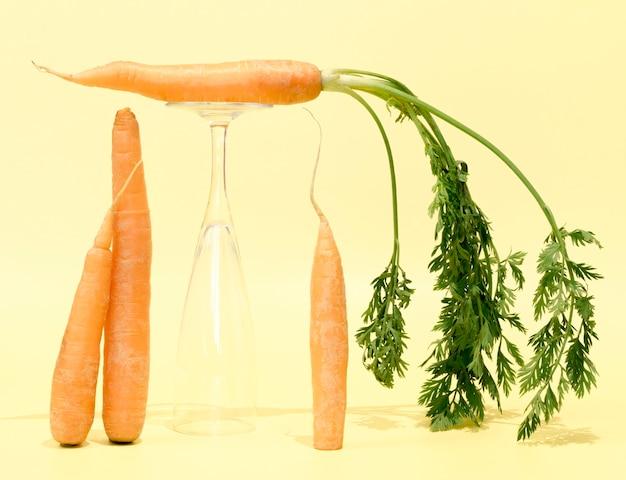 Vista frontal de cenouras com copo vazio