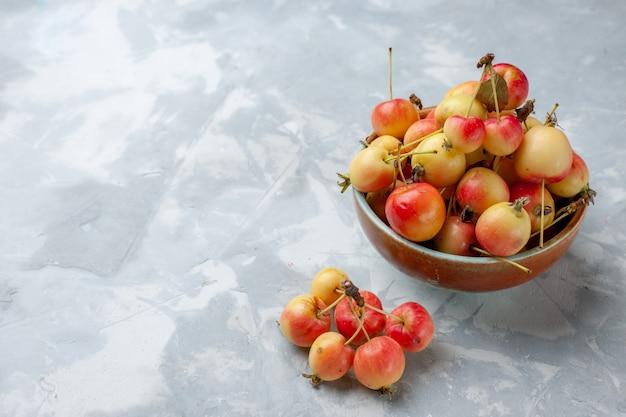 Vista frontal de cerejas doces frescas dentro do pote na mesa clara fruta fresca e suave cor suculenta