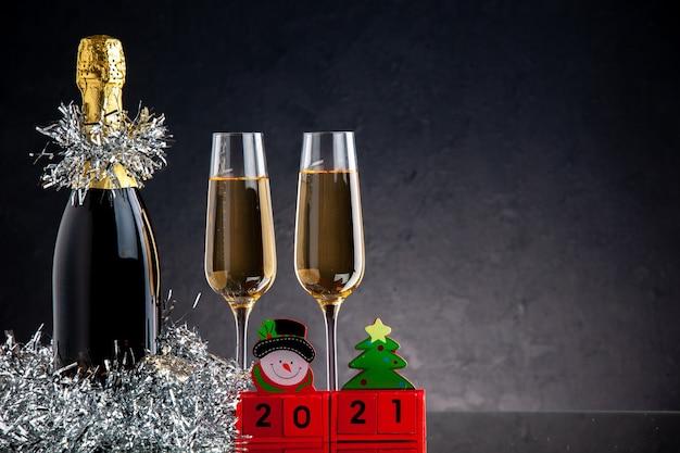 Vista frontal de champanhe em garrafa e taças de blocos de madeira na superfície escura