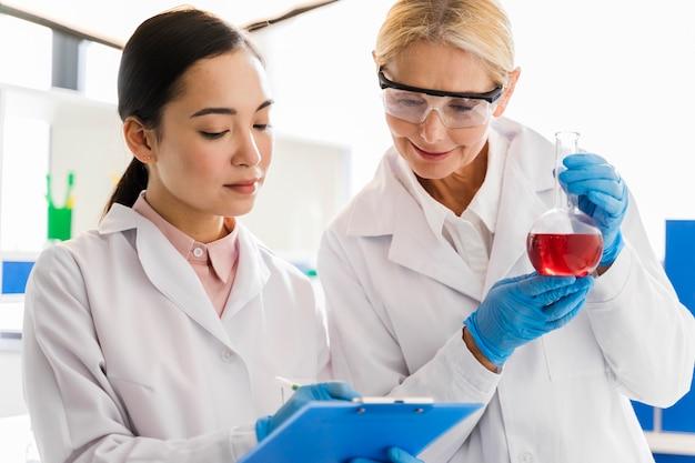 Vista frontal de cientistas femininos com luvas cirúrgicas em laboratório