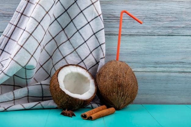 Vista frontal de cocos frescos com palha laranja na toalha xadrez na superfície cinza