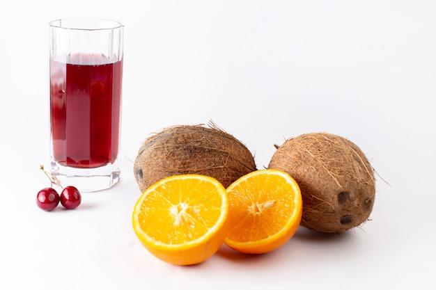 Vista frontal de cocos frescos junto com fatias de laranja e suco de cereja no branco