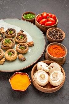 Vista frontal de cogumelos cozidos com tomates e temperos em um prato de mesa escuro cozinhando cogumelos