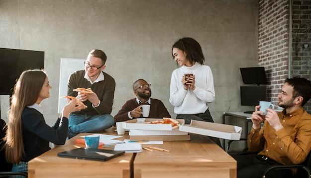 Vista frontal de colegas comendo pizza durante um intervalo de reunião de escritório