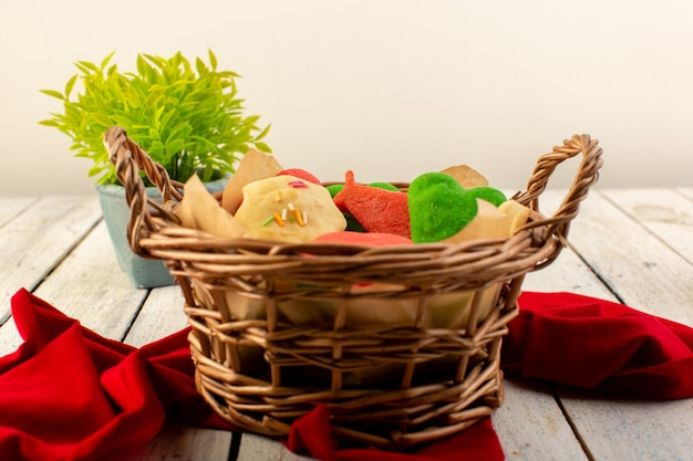 Vista frontal de coloridos deliciosos biscoitos diferentes formados dentro da cesta marrom