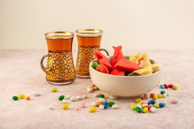 Vista frontal de coloridos deliciosos biscoitos diferentes formados dentro da placa com doces e xícaras de chá