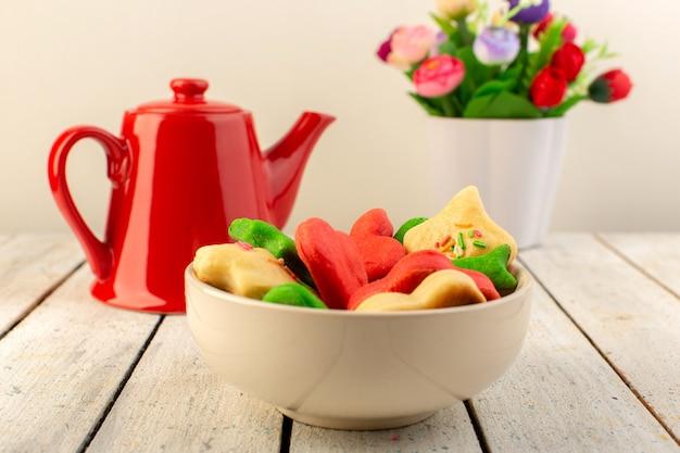 Vista frontal de cookies deliciosos coloridos diferentes formada dentro da placa com chaleira vermelha e flores