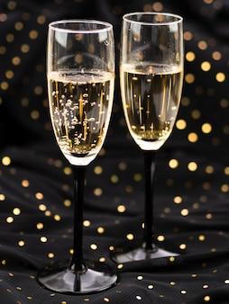 Vista frontal de copos borbulhantes de champanhe com pontos dourados