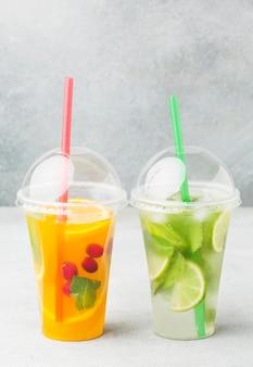 Vista frontal de copos com refrigerantes e canudos