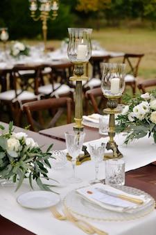 Vista frontal de copos e talheres servidos na mesa de madeira com composições florais e castiçais ao ar livre