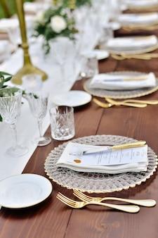 Vista frontal de copos e talheres servidos na mesa de madeira e placa de identificação impressa