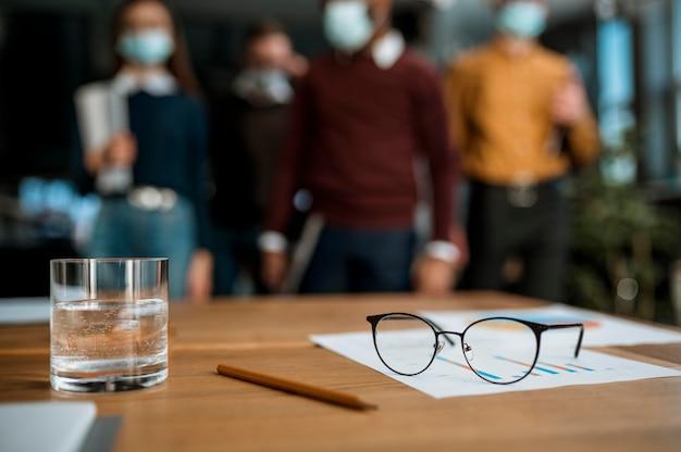 Vista frontal de copos e um copo de água na mesa durante uma reunião de escritório